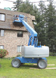 Building Maintenance and Hoist. An industrial hoist is used to repair siding on a building stock images