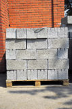 Building material. Brick on tray on background brick wall Stock Photo