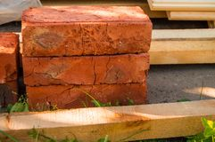 Building material for repairs in the garden-new red bricks, boards, lie on the grass.  stock image