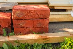 Building material for repairs in the garden-new red bricks, boards, lie on the grass.  stock photography