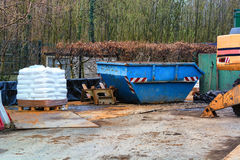 Building materials and objects on a construction site. Blue container an excavator and pallet with white bags on a construction site in the forest royalty free stock photos