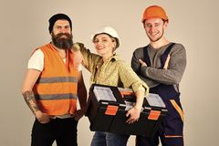 Building materials. Repair brigade concept. Company of cheerful workers, builder, repairer, plasterer. Teamwork, full. Service, brigade. Man and women with Royalty Free Stock Images