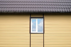 Building metal roof and wall finished with beige siding panels with white plastic window Stock Photography