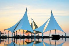 Building model is in the seashore public square. Under setting sun, soft membrane construction sailing ship modelling in seashore square, inverted image in water Royalty Free Stock Photos