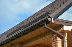 Building Modern House Construction with metal roof corner, rain gutter system and roof protection from snow Stock Photos