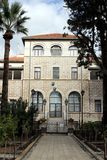 Building on the Mount of Beatitudes. A white masonry building with orange metal roof across from the cathedral on the Mount of Beatitudes with white, fluffy Royalty Free Stock Photos