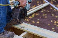 Building a new above ground deck, carpenter installing a wood floor outdoor terrace in new house. A man using pneumatic nailer gun patio backyard construction stock image