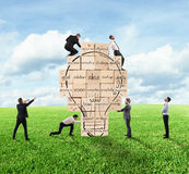 Building a new creative idea. Business person built together a big brick wall with drawn lightbulb Stock Photo