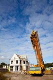 Building a new family home. Crane on  construction site building a new  home Royalty Free Stock Photography