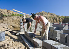 Building new house. Two workers building a new house, early stage with new walls going up Stock Photography