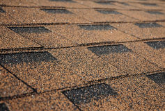 Building new house with asphalt shingle roof. Close up on brown roof shingles as a textured background Royalty Free Stock Photography