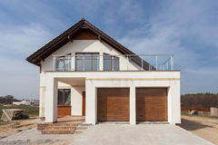 Building New House with Ceramic Tiles Roofing, Garage and balcony. Royalty Free Stock Photo