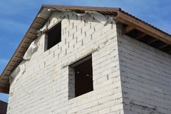 Building new house construction with aerated concrete blocks facade, attic room,  metal roofing. Close up stock photos
