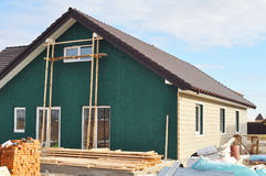 Building New House with Plastic Siding and Insulation Membrane on House Exterior Wall. Stock Images