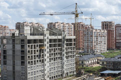 Building a new house in a residential area. Monolithic apartment building under construction on the background of a residential area Royalty Free Stock Photo