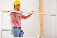Building a new house. Young man wearing protective gear and carrying some wood for a construction Stock Image