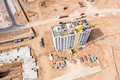 Building of new residential complex. yellow tower crane near block building. aerial top view stock images