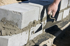 Building a new wall. A new wall is being built, a worker is laying another row of grey bricks and cementing them Royalty Free Stock Photos