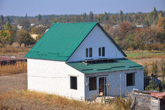 Building new white bricks country  house with green metal roof with roof protection from snow board on house construc Stock Photo