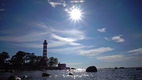 The building of the old beacon on the seashore against the background of the sky with brightly consecrating sun.Sunshine. The building of the old beacon on the stock footage