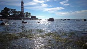 The building of the old beacon on the seashore against the background of the sky with brightly consecrating sun. Sunshine over a lighthouse. St. Petersburg stock video footage