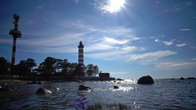 The building of the old beacon on the seashore against the background of the sky with brightly consecrating sun. Sunshine over a lighthouse. St. Petersburg stock footage