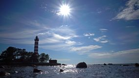 The building of the old beacon on the seashore against the background of the sky with brightly consecrating sun.Sunshine. Over a Lighthouse. St. Petersburg stock video