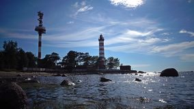 The building of the old beacon on the seashore against the background of the sky with brightly consecrating sun.Sunshine. Sunshine over a Lighthouse. St stock footage