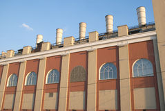 Building of old Power station with tubes on roof Stock Image