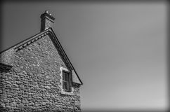 Building with one window and chimney. Black and white building with one window and chimney with the sky in the background stock photo