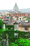The building is overgrown with vines. Behind the house you can see the St. Peter's Basilica. Stock Photos