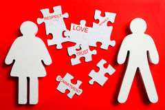 Building pieces of a relationship. Male and female figure with puzzle pieces between them on a red background royalty free stock photography