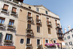 Building  with pink blooming petunia flowers  in Venice,Italy. Typical italian orange house  with pink blooming petunia flowers  in Venice ,Italy Royalty Free Stock Photo