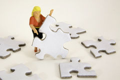 Building a Plan. Figurine of a woman holding a jigsaw puzzle piece standing amongst other pieces Stock Photos