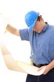 Building plan studying. Civil engineer wearing blue helmet studying a building plan over white stock photo