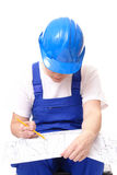 Building plan studying. Female civil engineer wearing blue helmet and jumpsuit studying building plan over white Stock Photos