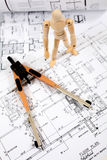 Building plans. Manikin standing on building plans,looking at a measuring tool royalty free stock image