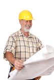Building plans. Cheerful construction worker analyzing some blueprints royalty free stock photos