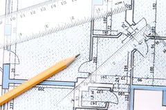 Building plans. Yellow pencil and setquare and protractor on top of a blue floor plan royalty free stock photo