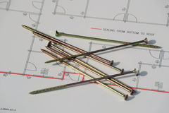 Building plans. Still life of building plans and huge screws for securing the base plate Royalty Free Stock Photos
