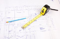 Building plans and tape measure. Set of building plans for a custom house with tape measure and pencil Royalty Free Stock Photo