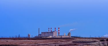 Power plant building with smoking pipes and glowing lights in th stock images