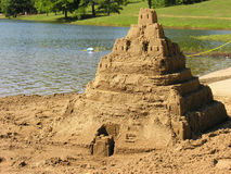 Building project. A large sandcastle at a deserted lake beach Stock Images