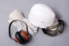 Building protective means. Goggles, helmet, ear-phones, protective gloves on a grey background Stock Images