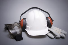 Building protective means. Goggles, helmet, ear-phones, protective gloves on a grey background Stock Image