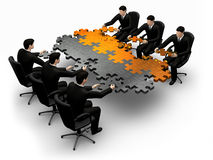 Building a puzzle. 3d business team work building a puzzle isolated over a white background Stock Photos