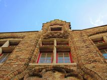Building with red windows and bricks and blue sky.  royalty free stock photography