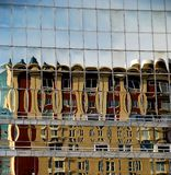 Building reflected in glass panels. The reflection of a building is broken up by the glass windows of the office building across the street.  Taken in San Diego Royalty Free Stock Image