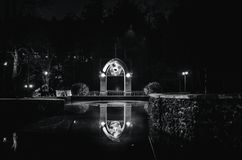 The building is reflected in the pond at night in the park royalty free stock photos