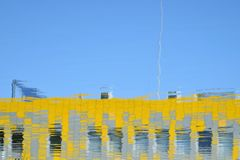 Building reflected in water. Blue sky and yellow building reflected in water Royalty Free Stock Images
